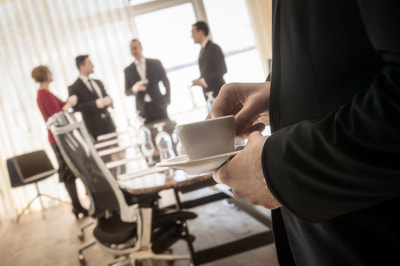 Business people in a conference meeting, sipping tea